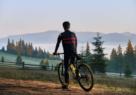 Back view of male cyclist in cycling suit standing with bike in the morning. Man bicyclist enjoying bicycle ride in foggy mountains. Concept of sport, biking and active leisure.