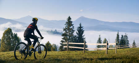 Man riding bicycle on grassy hill and looking at beautiful misty mountains. Male bicyclist enjoying panoramic view of majestic mountains during bicycle ride. Concept of sport, bicycling and nature. Stok Fotoğraf