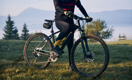 Cropped view of man in cycling suit riding bicycle on grassy hill. View of majestic mountains on the blurred background. Concept of sport, bicycling and nature. Stok Fotoğraf