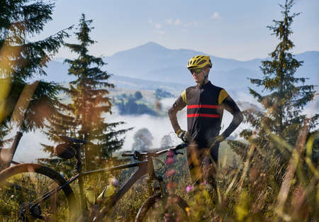 Cyclist wearing uniform and helmet, standing on grassy hill. Beautiful mountains landscape on background. Early morning. Bicycle on blurred foreground. Concept of unity with nature Stok Fotoğraf
