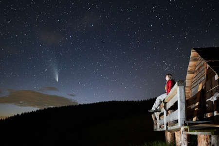 Female traveler sitting on wooden plank and looking at majestic night sky with stars and comet Neowise. Young woman hiker enjoying fantastic view of blue starry sky while resting outside forest house.