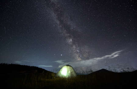 Amazing starry night sky in the mountains and illuminated tent at campsite. Millions of stars over single tent in the middle of mountain meadow. Concept of mountain retreat