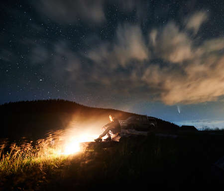 Fantastic view of night starry sky over grassy hill with male hiker near campfire. Man traveler looking at bonfire while sitting near car under beautiful sky with stars, clouds and comet Neowise.
