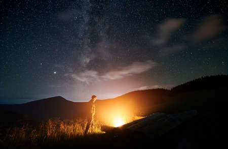 Side view of silhouette of man walking in mountains and lighting fire. Male tourist is resting near bonfire in forest in evening. Concept of healthy lifestyle.
