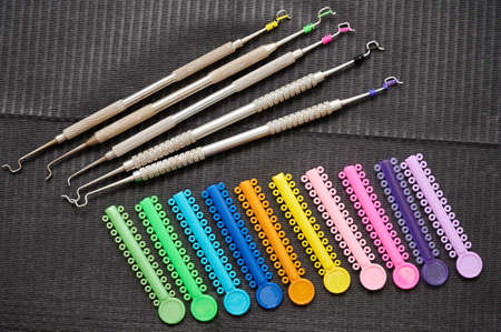 Colorful orthodontic ligatures and stainless steel instruments for procedure of attaching braces to teeth. Black napkin with orthodontic tools and multicolored rubber bands for braces.