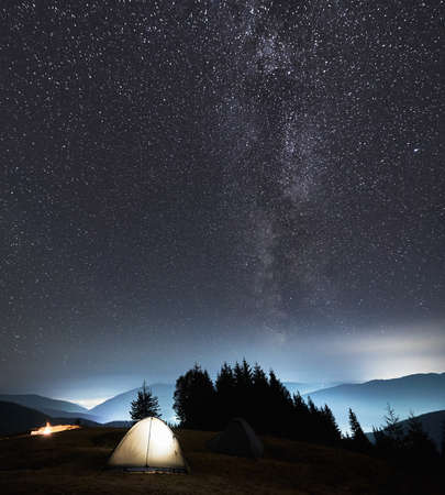 Two tourist tents set up on mountain hill under night starry sky against background of magical Milky Way, shadows of trees and contours of the mountain beskids. Concept of night camping and astronomy. Stock fotó