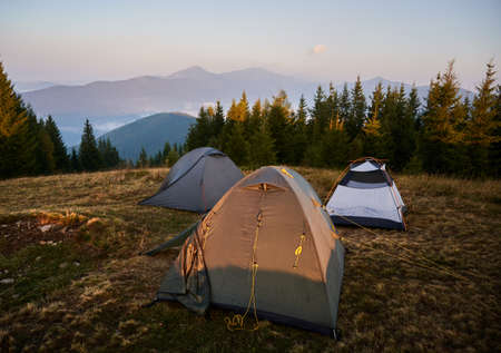 Tourist camp with three tents set up on meadow near forest. Morning sunlight on tent and surrounding nature. Silhouettes of high mountains on background.