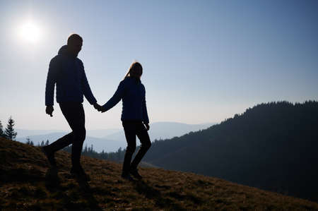Full length of happy couple in love holding hands and smiling while walking down grassy hill early in the morning. Silhouettes of young man and woman travelers spending time together in mountains.