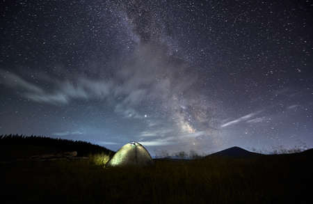 Front view of beautiful landscape of campsite in mountains. Scenery of two tents near forest at night under starry sky. Concept of leisure in mountains. Stok Fotoğraf