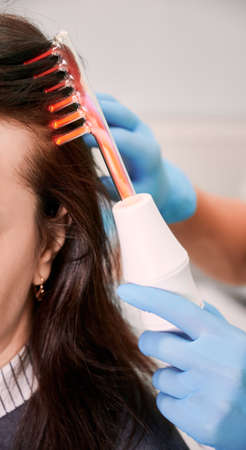 Close up of doctor trichologist hand in sterile gloves brushing female client hair with laser hair growth device. Woman receiving hair treatment laser therapy in medical center. Concept of beauty.