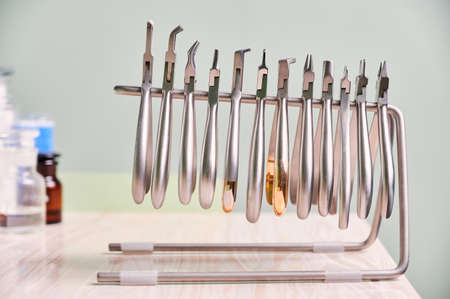 Set of different stainless steel instruments for braces. Silver removing pliers, cutters, removers, other orthodontic tools on wooden table in dental clinic. Concept of dentistry, dental instruments.