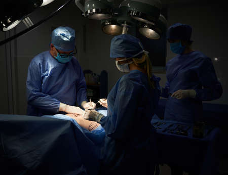 Medical team doing aesthetic plastic surgery in operating room with dim light. Surgeon and assistants performing cosmetic surgery and using medical instruments. Concept of medicine and plastic surgery