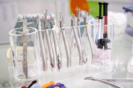 Close-up snapshot of dental tools hanging on transparent stand. Orthodontic tongs and forceps on the table. Steel instruments for dental use. Concept of dentistry, medical instruments