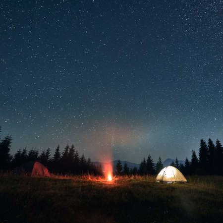 Night camping under amazing starry sky. Wide angle view on beautiful landscape in the mountains. Two tents, one glowing, and campfire, wall of spruces on background. Concept of travelling.