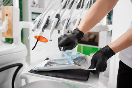 Close up of dentist hands in black sterile gloves opening package with sterile dental instruments. Doctor preparing instruments for dental procedure. Concept of dentistry, stomatology and dental tools