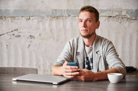 Portrait of handsome young man student with beard sitting with laptop and cup coffee and holding smartphone. Concept of working or studying in phone.