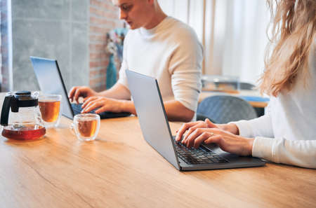 Side view of couple working on laptops in kitchen. Man and woman are typing on computers near table with two cups of tea. Concept of remote job.