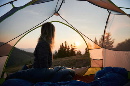 Hiker woman basking by warm sun rays at dawn in the mountains, being in tent in her campsite. Cloudless sky, trees and mountain hills on the background.