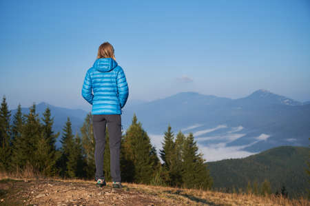 Rear view of female traveler standing on top of mountain hill and looking at the panorama of mountain hills covered with thick white fog below. Concept of travelling, hiking and nature.