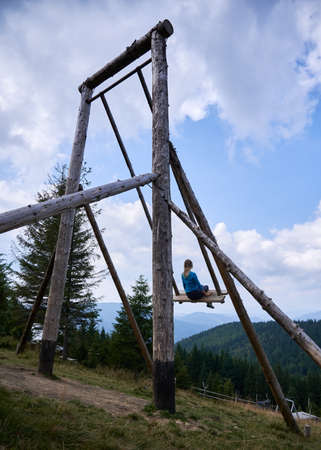 Very large swing made of wood and mounted on mountain hill on which girl with white hair having fun and watching on nature scenery. Stok Fotoğraf