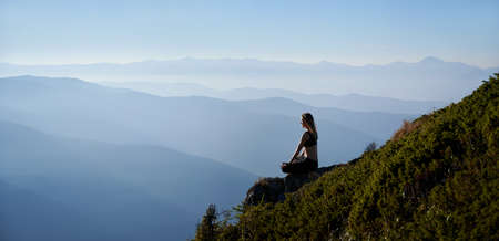 Panoramic view. Fit young woman sitting on grassy hill in lotus position while mediating outdoors in the morning. Sporty woman doing meditation yoga exercise in the mountains. Copy space. Stok Fotoğraf