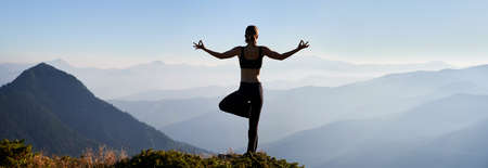 Back view of young woman doing meditation on fresh air. Concept of harmony with nature. Panorama