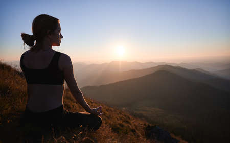 Back view of fit young woman sitting in lotus position and meditating while looking at beautiful sunrise in mountains. Sporty woman doing meditation yoga exercise on grassy hill. Stok Fotoğraf