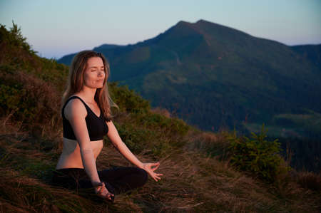 Side view of woman practicing yoga in Lotus pose in the mountains. Meditating female is taking a deep breath and smiling. Concept of relaxation.