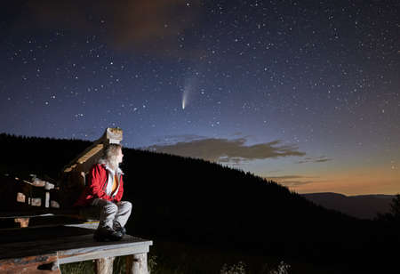 Side view of woman sitting on wooden bench in mountains and watching starry sky. Female in red jacket is relaxing near forest and looking on comet Neowise. Concept of resting in mountains.
