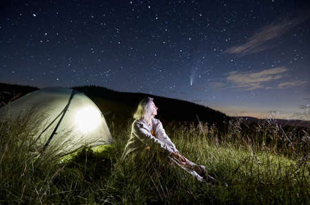 Female traveler sitting on grass, enjoying fantastic view of night sky with stars and comet Neowise. Magnificent scenery of night starry sky over grassy hill with tourist tent and blonde woman hiker.