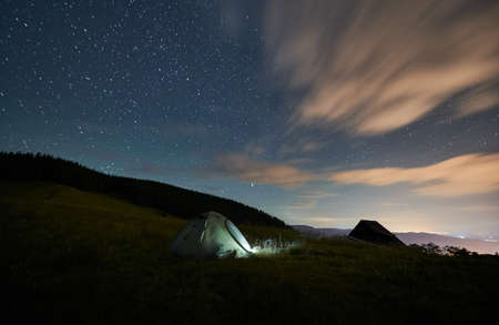 Front view of scenery of tourist tent near forest under starry sky. Somebody is camping in mountains at night. Concept of nature.