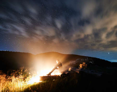 Side view of young man sitting and basking near cozy bonfire on fresh air. Concept of relaxing in mountains and enjoying beautiful starry sky at night.