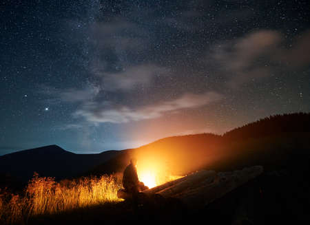 Tourist man resting on nature and enjoying bonfire under starry sky. Concept of relaxing on fresh air and looking at night sky with stars.