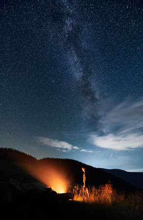 Man hiker looking at bright bonfire while standing under blue night sky with stars and Milky Way. Starry sky over grassy hill with male traveler near campfire. Concept of night camping and astronomy.