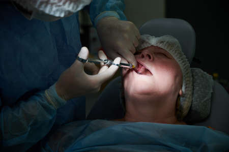Close up of doctor hands in gloves injecting dose of anesthetic medicine with carpool syringe. Dentist inserting needle into woman gum while doing local anesthesia injection before dental procedure.