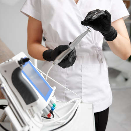 Dentist wearing white uniform and black gloves, working with all-in-one device concept for mechanical root canal treatment. Concept of modern dental endodontic equipment Stok Fotoğraf