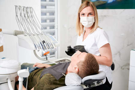 Horizontal snapshot of a pretty, young female dentist, wearing uniform, face mask, rubber gloves, sitting at her working place in well equipped dental office. Male patient during dentists visit