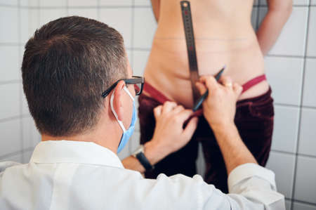 Close up of plastic surgeon measuring woman belly before plastic surgery. Doctor using ruler and marker pen while checking female patient abdomen before aesthetic surgery. Concept of abdominoplasty. Stok Fotoğraf