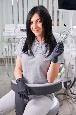 Female dentist in sterile gloves holding tools for dental treatment. Woman doctor smiling to camera while demonstrating dental instruments. Concept of dentistry, stomatology and dental medicine. Stok Fotoğraf