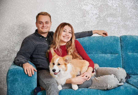 Happy couple sitting on cozy blue sofa with lovely orange white dog. Concept of resting and relaxing with good mood at home.