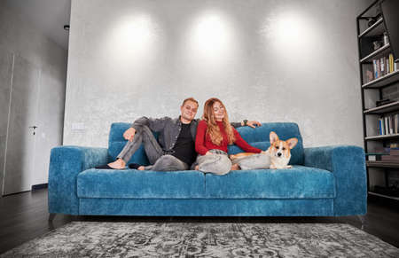 Joyful young woman and man looking at camera and smiling while sitting on sofa with adorable Corgi dog. Loving happy couple resting on couch with cute dog while spending time together at home. Stok Fotoğraf