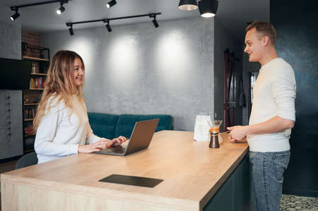 Side view of young pretty woman working in laptop and young man doing tasty coffee in turk at home in modern kitchen with good lighting. Concept of working in laptop and break for coffee at home. Stok Fotoğraf