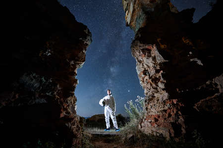 Portrait of spaceman in white suit holding helmet and standing between abandoned walls at night. Man in spacesuit under starry sky with Milky way.