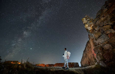 Spaceman in white suit holding helmet and looking in starry sky with Milky way. Man in spacesuit exploring abandoned area at night. Concept of astronomy.