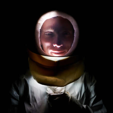 Close-up portrait of smiling spaceman in white suit and helmet in darkness. Man in spacesuit is posing on black background at night. Concept of cosmonaut. Stok Fotoğraf