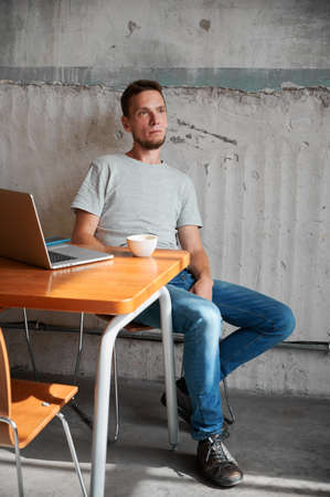 Male sitting by table with laptop and cup of coffee. Young man is resting after work online. Concept of home office.