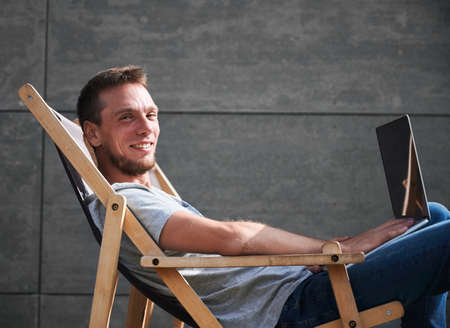 Smiling male sitting on wooden chair and typing on laptop. Young man working on laptop outdoor under sunny weather. Concept of comfortable workplace. Stok Fotoğraf
