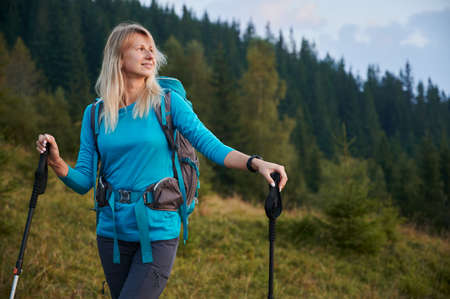 Joyful female traveler looking at beautiful mountains and smiling while holding trekking poles. Charming young woman hiker carrying backpack and holding hiking sticks while standing on grassy hill.