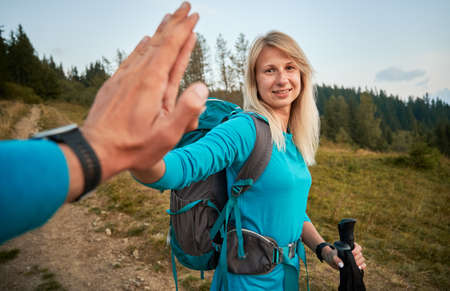 Point of view shot female hiker with backpack giving high five and smiling while holding trekking poles. Woman and man slapping hands while hiking together in mountains. Concept of relationships.