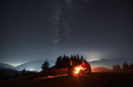 Young man sitting on mountain hill by campfire playing guitar for his beloved under night starry sky with Milky way. Silhouettes of trees, mountains and light from surrounding villages on the backdrop Stok Fotoğraf